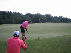 Golfers at the Putting Competition hope for a hole in one.